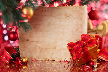 Gift and old parchment against Christmas background.