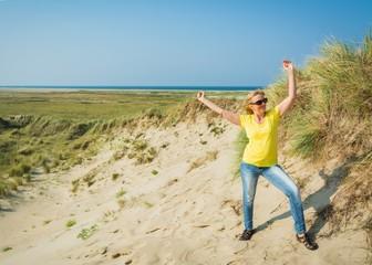Frau fühlt sich wohl in den Dünen am Strand