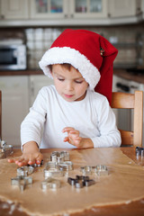 Adorable little boy, preparing cookies for christmas