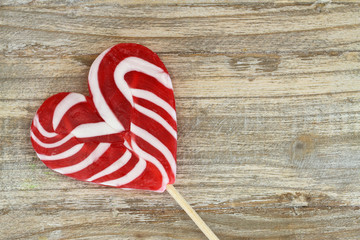 Heart shaped lollipop on wooden surface with copy space