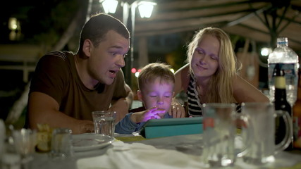 Family with tablet PC in outdoor cafe