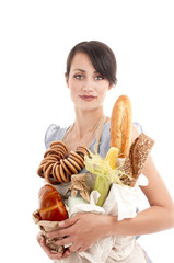 Young beautiful woman holding bags with fresh  bread and other f