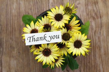 Thank you card with yellow daisies on wooden surface