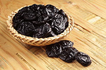 Prunes in a wicker bowl and near