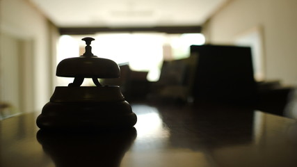 Woman ringing a bell on reception in hotel