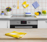 Fototapety Wooden table with yellow napkin on kitchen background