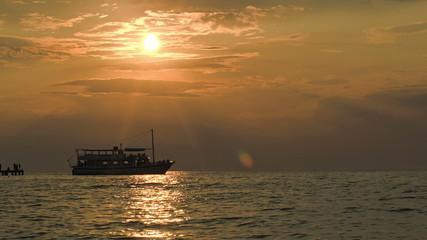 Tourist ship leaving pier at sunset