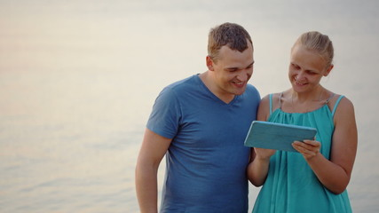 Young couple using tablet computer by the sea