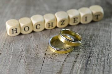 Trauringe auf Holz mit Buchstaben