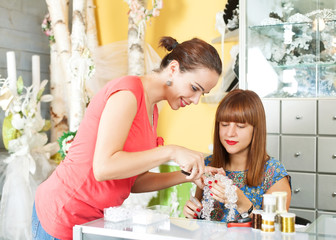 Two woman making jewelry in a accessory shop