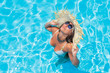 Woman with straw hat in the swimming pool