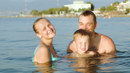 Happy parents and son bathing in sea on resort