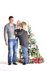 Mother, father and their small child stand near Christmas tree