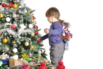 Сhild about a Christmas tree with two red lamps with backpack