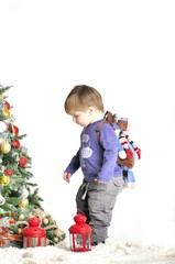 Small child about Christmas tree with two lamps with backpack
