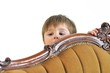 The small child hides behind a sofa and looks out