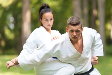 Young Woman and Man Practicing Martial Arts Outdoors