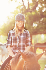 Beautiful young woman riding on a brown horse