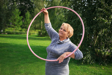 Portrait of happy pretty senior woman exercising with hula hoop