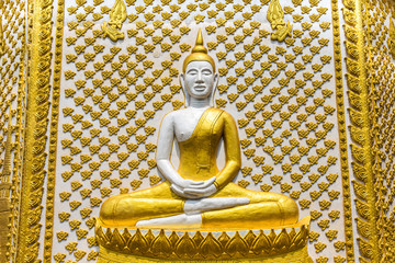 ancient buddha statue sitting on wall of pagoda in thai temple
