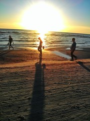 Boys walking barefoot at sunset along the beach
