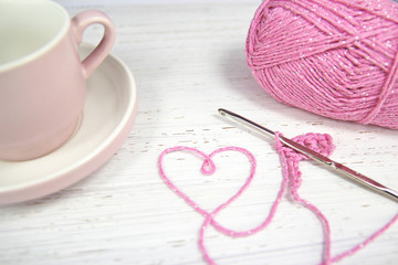 pink crochet background with yarn heart and coffee cup