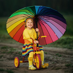little girl on the bicycle with umbrella