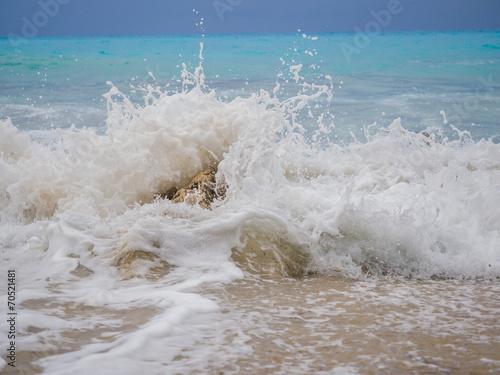 Leinwanddruck Bild waves breaking on a stony beach
