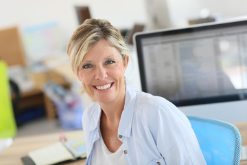 Portrait of cheerful blond woman in office