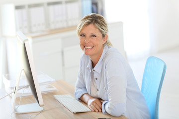 Mature businesswoman sitting in front of desktop