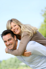 Cheerful mature man giving piggyback ride to woman