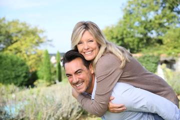 Cheerful mature man giving piggyback ride to woman