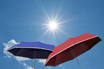 Zwei Schirme vor blauem Himmel mit strahlendem Sonnenschein