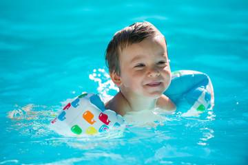 enfant avec des brassards- à la piscine