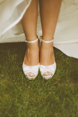 Bride's White Shoes on a Grass Field