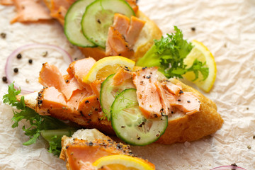 Sandwich with smoked salmon, cucumber, lemon and black pepper