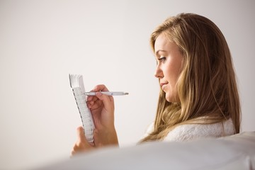 Pretty blonde relaxing on the couch writing in notepad