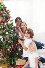 Parents and their children decorating a christmas tree