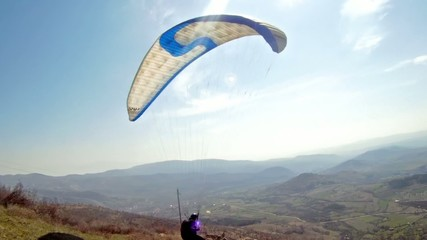 Paraglider taking off from a mountain range