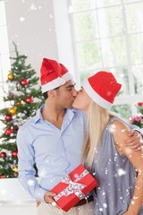 Composite image of kissing couple at christmas