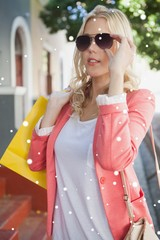 Pretty blonde in sunglasses holding shopping bags