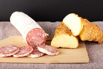 Salami and bread on cutting board