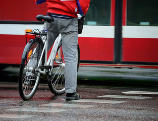 Man in red, in rain, on bike, waiting, in traffic