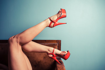 Woman in stripper heels on sofa
