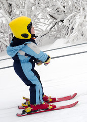 Skiing child on rope lift