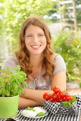 Junge Frau mit Tomaten und Mozzarella