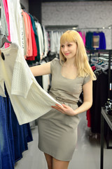 Girl tries on a new dress in the shop