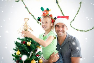 Happy father and daughter decorating together the christmas tree