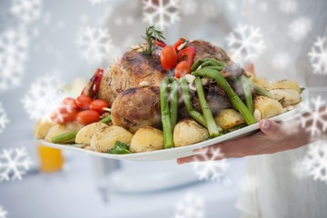 Composite image of woman presenting a roast dinner