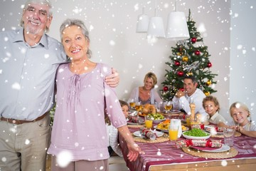 Composite image of grandparents standing by the dinner table